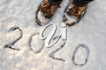 Brown leather shoes standing on the snow with inscription 2020. New Year holiday background.