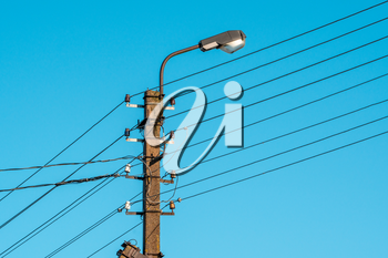 High voltage electric pole with lamp over a sky background