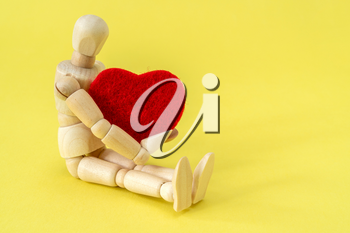 Wooden man holding a red heart as symbol of love. Valentine day.