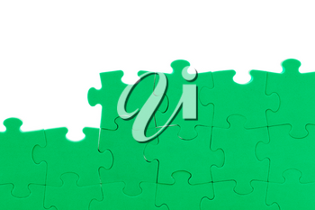 Unfinished green jigsaw puzzle wall. Copy space.