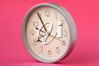 Modern wall clock isolated on red background