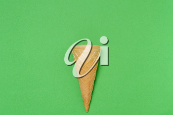 Sweet wafer cone on green background
