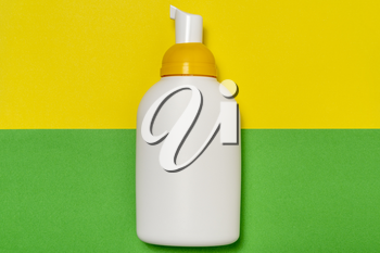 Plastic white bottle with dispenser pump  on colored background