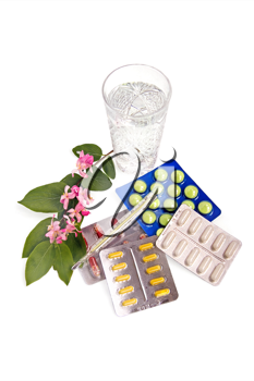 A set of tablets and capsules with a thermometer, the water in a crystal glass and a branch with pink flowers and green leaves on a white background