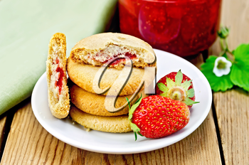 A stack of cookies filled with jam and strawberries on a plate, a jar of strawberry jam on the background of wooden boards