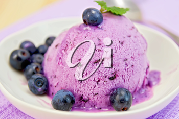 Blueberry ice cream with mint leaves in a bowl with berries on a background of purple cloth and wooden boards