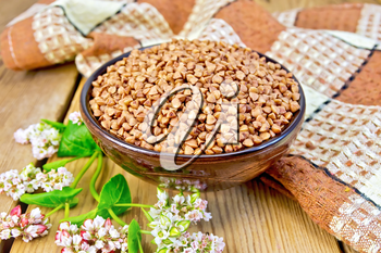 Buckwheat in a bowl with a flower buckwheat and a napkin on a wooden boards background