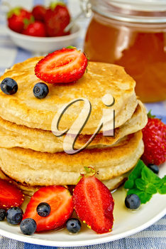 A stack of pancakes with strawberries, blueberries and honey on a white plate, a jar of honey on a linen tablecloth background