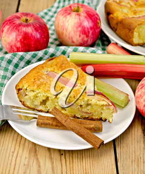 A piece of sweet cake with rhubarb and apples, cinnamon, napkin on a wooden boards background
