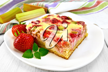 Piece of pie with strawberries, rhubarb and cream sauce, fork, strawberry, mint in white plate, a napkin on the background light wooden boards