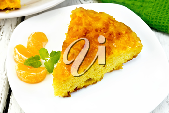 Piece of tart  with mandarin, mint, tangerine slices in white plate, a towel on the background light wooden boards
