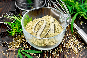 Hemp flour in a glass cup, mixer, sieve and molds for cookies, leaves and seeds of cannabis on a background of dark wood planks