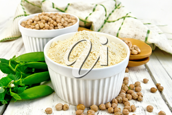 Flour chickpeas and chick-pea in white bowls and spoons, pods of green beans, a towel on the background of wooden boards