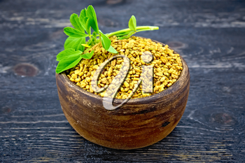 Fenugreek in a clay bowl with green leaves on a wooden plank background