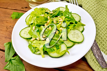 Salad of spinach, fresh cucumbers, rukkola salad, cedar nuts and green onions, seasoned with vegetable oil in a plate, napkin and fork on a plank background