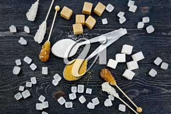Sugar white and brown granulated in spoons, crystal and cubes on the background of a black wooden board from above