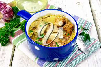 Fish soup with tomatoes, potatoes, peppers, croutons and cream in a blue bowl on a napkin, parsley and garlic on a light wooden board background