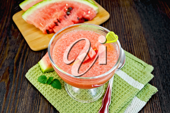 Jelly airy watermelon in a glass bowl, spoon and mint on a green towel against a dark wooden board