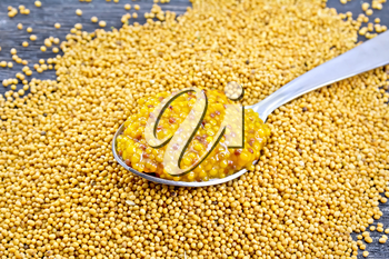 Mustard Dijon sauce in a metal spoon on the seeds on wooden board background