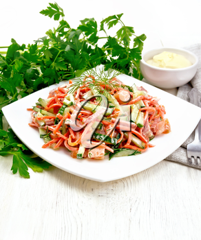 Salad from smoked sausage, spicy carrot, tomato, cucumber and spices, dressed with mayonnaise, napkin, fork and parsley on a wooden board background