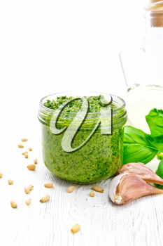 Pesto sauce in a glass jar, pine nuts, garlic, green basil and olive oil in a carafe on a background of white wooden board