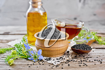 Flour of black caraway in a bowl, seeds in a spoon, oil in a bottle and sauceboat on burlap, sprigs of Nigella sativa with blue flowers and leaves on wooden board
