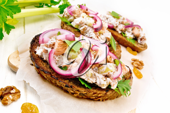 Salmon, petiole celery, raisins, walnuts, red onions and curd cheese salad on toasted bread with green lettuce leaves on parchment on a light wooden board background