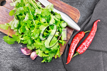Fresh cilantro, knife, garlic, hot red pepper and napkin against a wooden board background from above