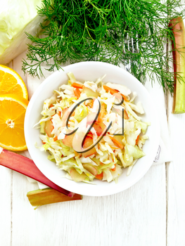 Fresh cabbage, carrot and rhubarb salad with orange juice, honey and mayonnaise dressing in a plate on a towel, dill and fork on wooden board background from above
