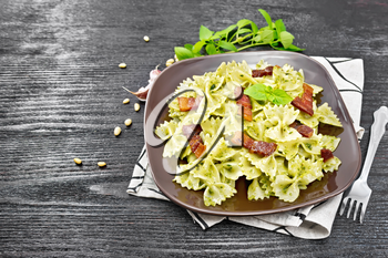 Farfalle pasta with pesto sauce, fried bacon and basil in a plate on a towel on wooden board background