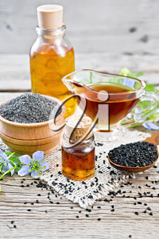 Nigella sativa oil in vial, gravy boat and bottle, seeds in a spoon and black cumin flour in a bowl on burlap, kalingi twigs with blue flowers and green leaves on background of an old wooden board