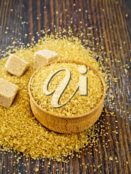 Granulated brown sugar in a bowl and on a table, cubes on wooden board background