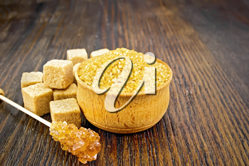 Granulated brown sugar in a bowl, crystalline on a stick and diced on a dark wooden board background