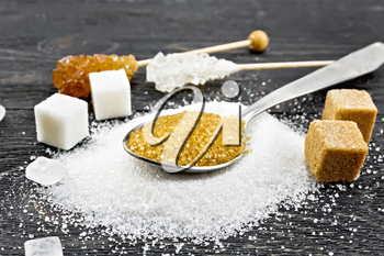 Brown granulated sugar in a metal spoon, white granulated sugar on a table, crystalline and cubes on wooden board background