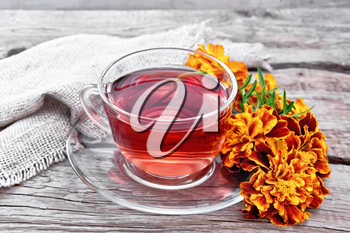 Marigold herbal tea in a glass cup and saucer, fresh flowers, sackcloth napkin on wooden board background