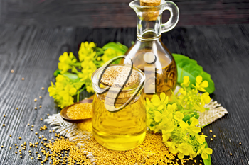 Mustard oil in a glass jar and decanter, mustard grains on a burlap napkin, flowers and leaves on dark wooden board background