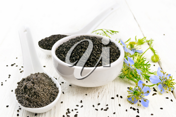 Black cumin seeds in a bowl, flour and seeds in spoons, kalingi sprigs with blue flowers and green leaves on a wooden board background