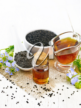 Nigella sativa oil in vial and gravy boat, seeds in a spoon and black cumin flour in a bowl on burlap, kalingi twigs with blue flowers and green leaves on light wooden board background