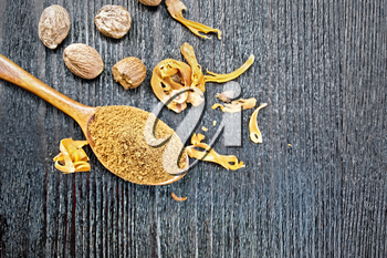 Ground nutmeg in a spoon, whole nuts and dried nutmeg arillus on a wooden board background from above