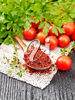 Dried tomato flakes in a spoon on burlap, fresh small tomatoes, parsley and thyme on wooden board background