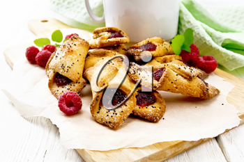Cookies with raspberry jam, berries and mint on parchment on a plank, cup with coffee and napkin on wooden board background
