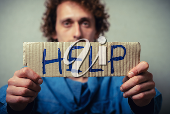 Curly man with a kraft cardboard with text donate help. On a gray background.
