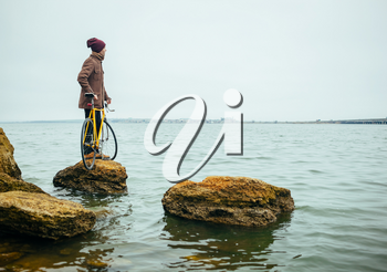 a young man with a bicycle stands on stone in lake