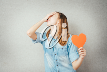 girl holding a paper heart and suffers