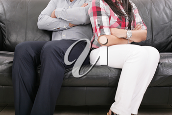 Couple sitting of the couch having problems in their relationship