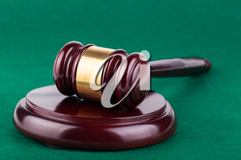 Wooden brown gavel on a green background