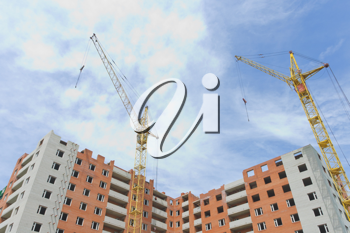 Construction area: two cranes and incomplete high-riser against blue sky background