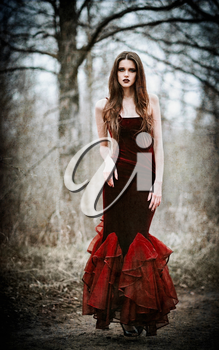 A beautiful sad girl in the autumnal forest. Grunge texture effect