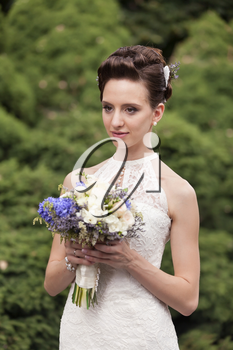 Young bride with bouquet in the park