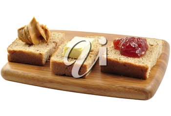 bread with jelly , peanut butter and butter on a cutting board